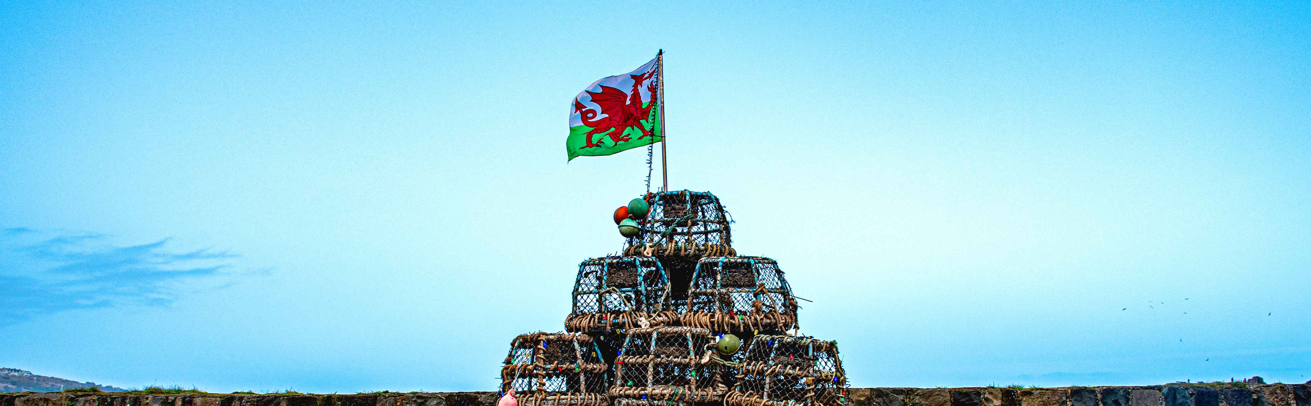 Welsh flag flying above a pyramid of lobster pots.