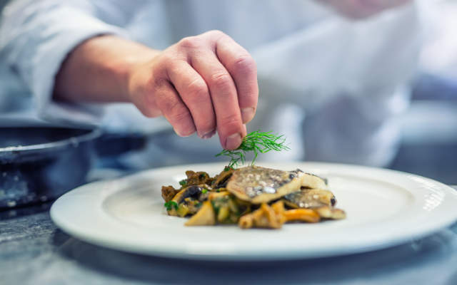 A hand sprinkling garnish onto a plated fish dinner.